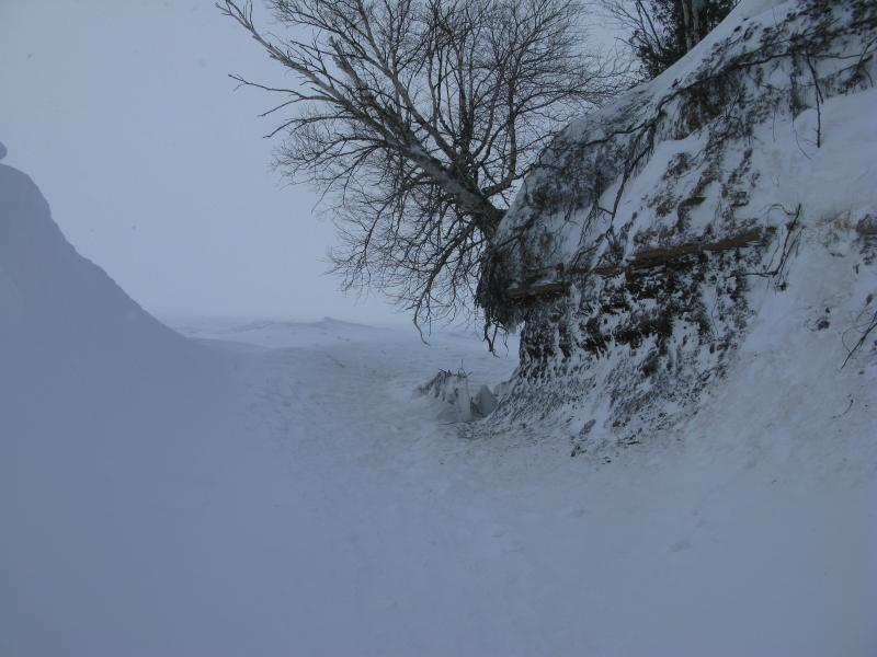 Narrow path between rock and snow