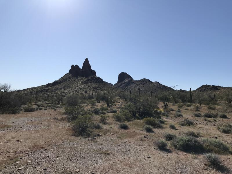 Flat desert surrounding jagged outcroppings