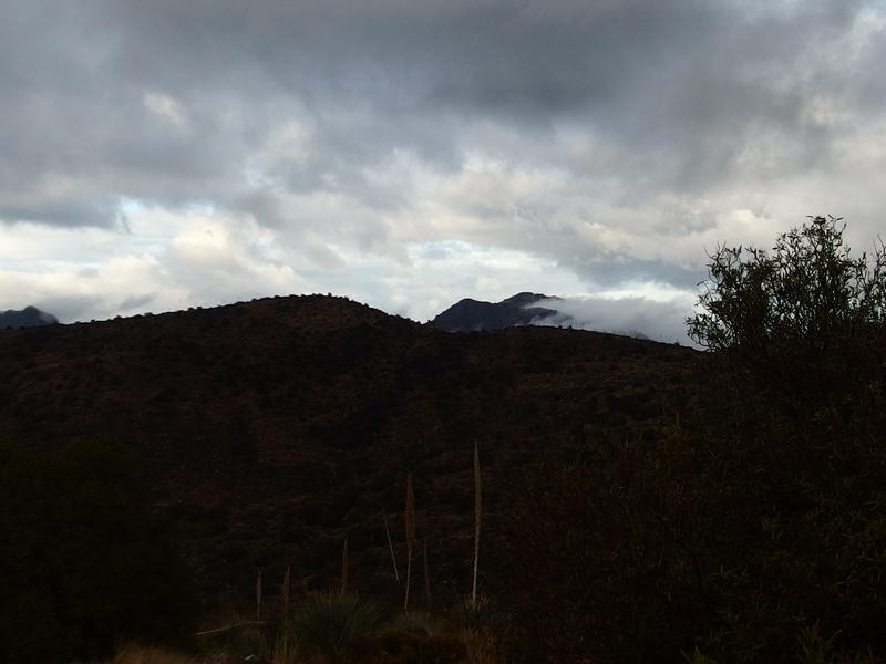 Clouds roiling from the dark mountains