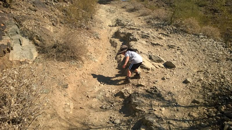 Noah carefully making his way down the rugged descent