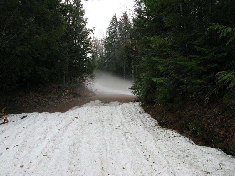 Snow and steam rising from the narrow road