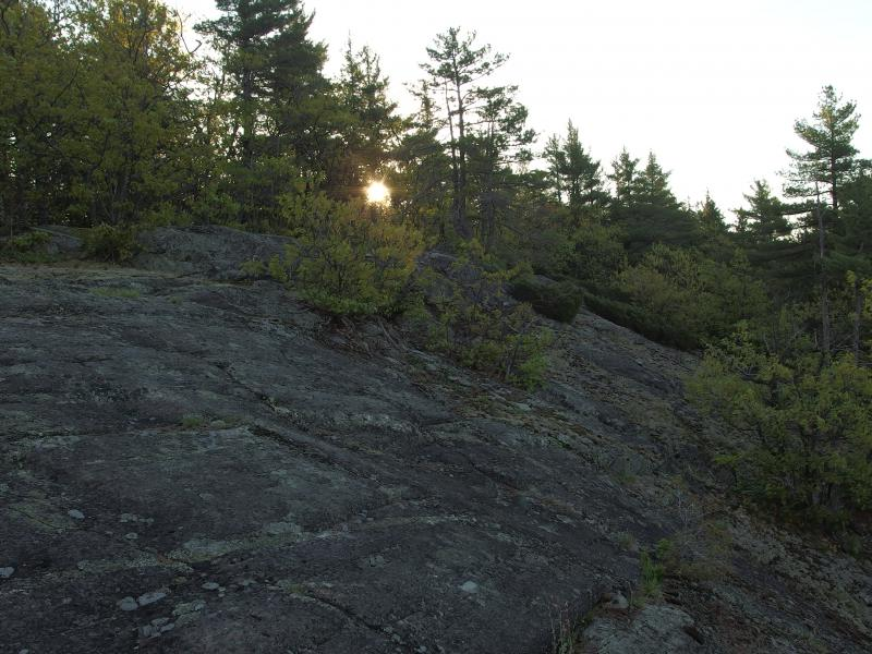 Peeking sun over the rock